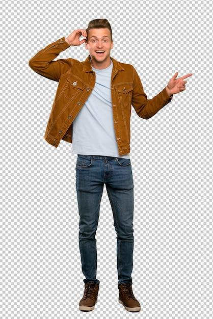 Blonder gutaussehender mann überrascht und finger auf die seite zeigend Premium PSD