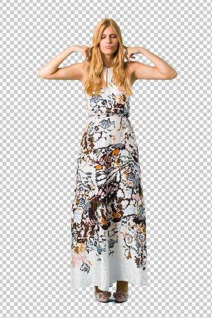 Blondes junges mädchen in einem sommerkleid, das beide ohren mit den händen bedeckt. frustrierter ausdruck Premium PSD