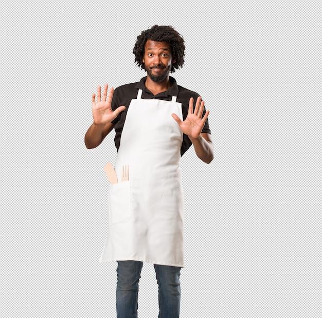 Der hübsche afroamerikanerbäcker, der ernst und entschlossen ist, hand in front setzend, stoppen geste, verweigern konzept Premium PSD