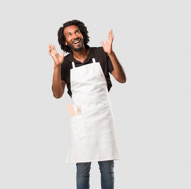 Der hübsche afroamerikanerbäcker, der überrascht und entsetzt ist und mit großen augen, aufgeregt durch ein angebot oder durch einen neuen job, schaut, gewinnen konzept Premium PSD