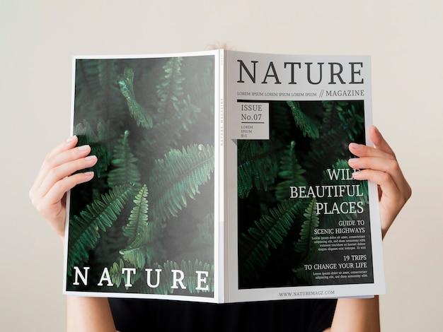 Die hand der frau, die einen naturzeitschriftenspott hochhält Kostenlosen PSD