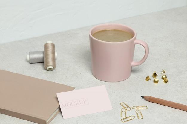 Die modellvisitenkarte, das rosa buch, der goldene bleistift, die büroklammern, die stifte und die fäden, tasse kaffee auf granitbeschaffenheit Premium PSD