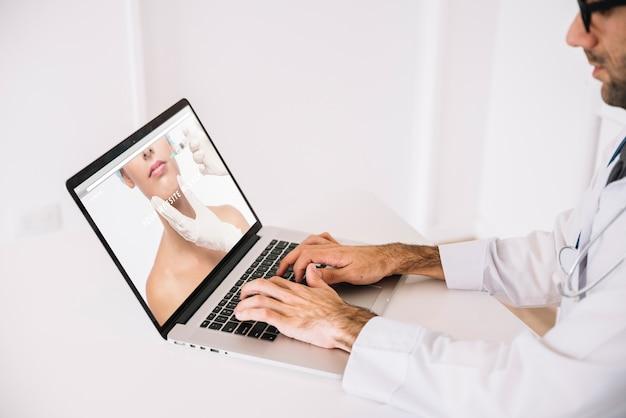 Doktor, der mit laptop arbeitet Kostenlosen PSD