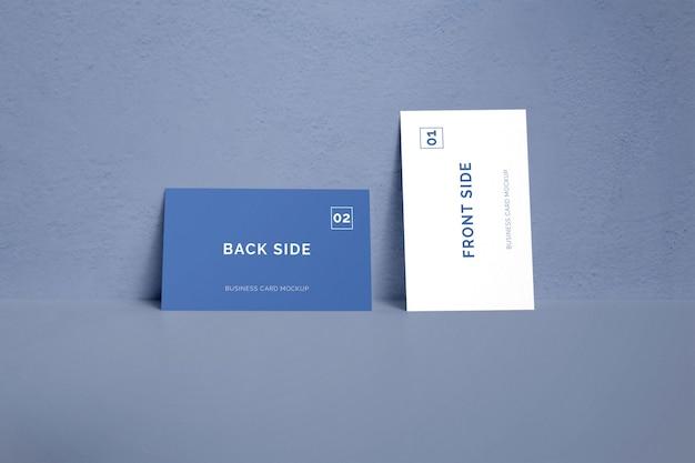 Doppelseitige visitenkarte, die auf einem wandmodell liegt Premium PSD