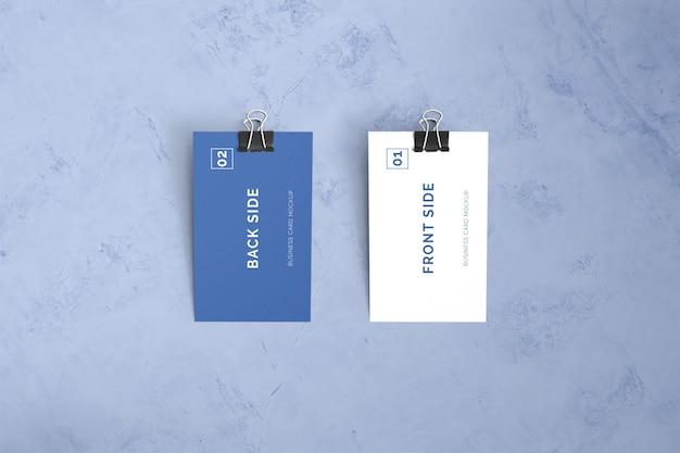Doppelseitige visitenkarte, die auf marmor mit büroklammermodell legt Premium PSD