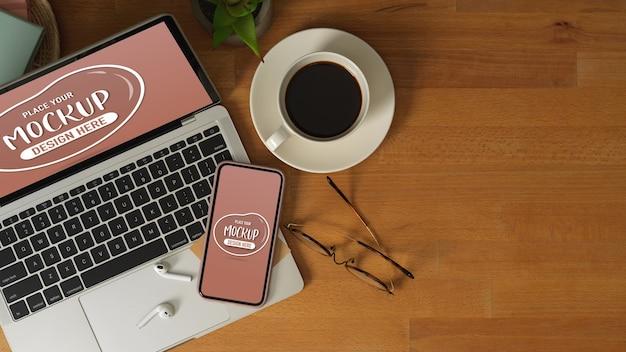 Draufsicht auf arbeitstisch mit mock-up-laptop, smartphone, brille, kaffeetasse und kopierraum Premium PSD