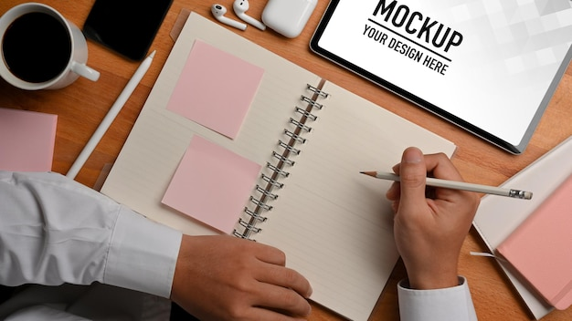 Draufsicht der männlichen hand, die zeitplanbuch und kaffeetasse mit tablettenmodell hält Premium PSD