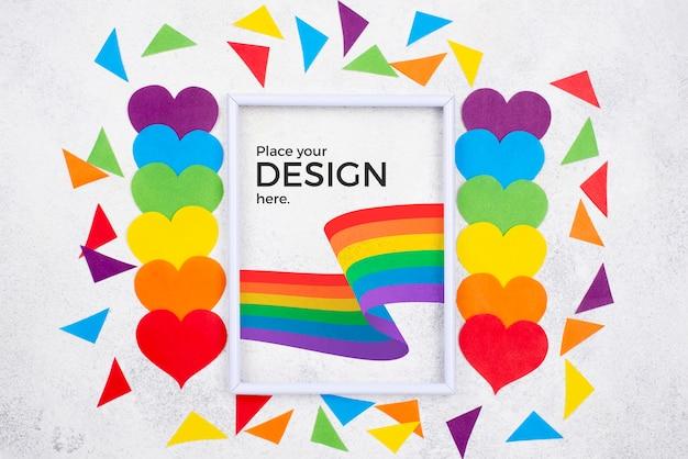 Draufsicht der regenbogenfarbenen herzen mit flaggen- und papierformen Kostenlosen PSD