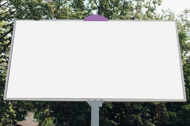 Eine große werbetafel mit einem werbebild im park auf der straße Kostenlosen PSD
