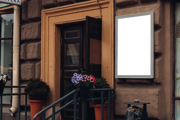 Eine kleine werbetafel, modell auf einem gebäude in der innenstadt mit einer ladenwerbung Premium PSD