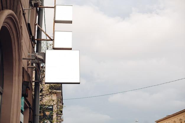 Eine mittelgroße werbetafel in einer stadtstraße zieht die aufmerksamkeit auf sich Kostenlosen PSD