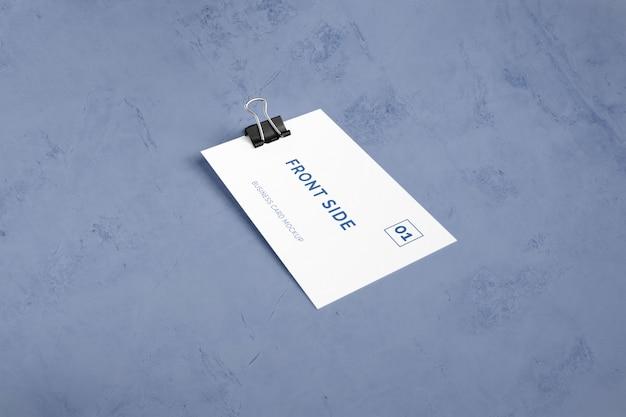 Einzelne visitenkarte, die auf marmor mit büroklammermodell legt Premium PSD