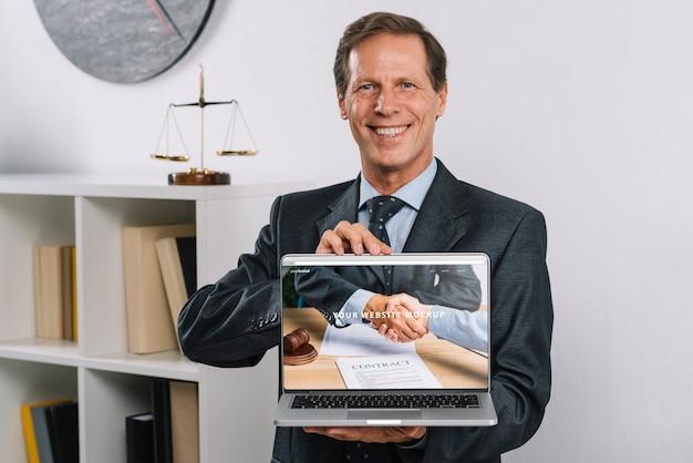 Eleganter geschäftsmann, der laptopmodell darstellt Kostenlosen PSD