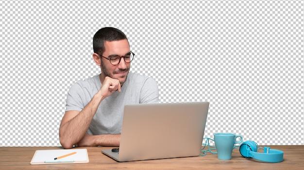 Erfüllter junger mann, der an seinem schreibtisch sitzt Premium PSD