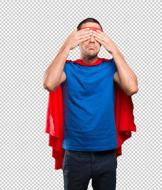Erschrockener superheld, der seine augen bedeckt Premium PSD