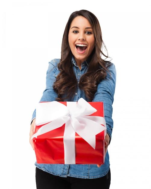 Excited mädchen ein geschenk mit einem weißen bogen halten Kostenlosen PSD