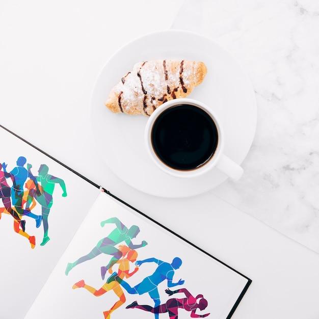 Flach lag offenes buchmodell mit kaffee und croissant auf Kostenlosen PSD