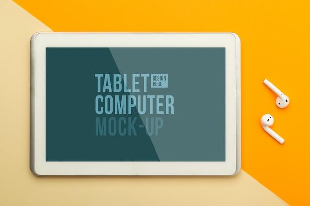 Flache lage, draufsicht auf orange bürotisch schreibtisch mit tablet-computer-modellvorlage für ihr design und drahtlose kopfhörer. moderner arbeitsraum Premium PSD