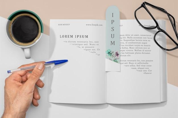 Flaches offenes buch und lesezeichenmodell mit kaffee Kostenlosen PSD