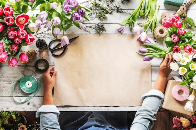 Florist, der leeres design space paper auf hölzernem tablee zeigt Kostenlosen PSD