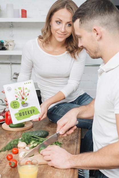 Frau, die buch in der küche hält, während mann kocht Kostenlosen PSD