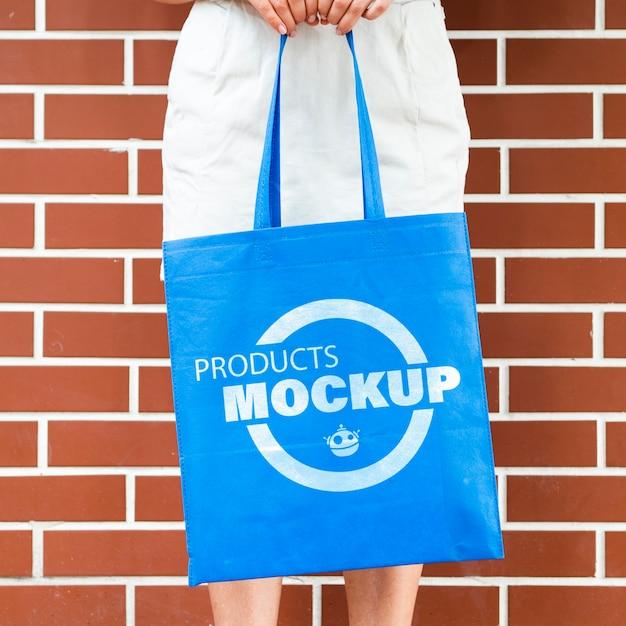 Frau, die ein einfaches blaues taschenmodell hält Kostenlosen PSD