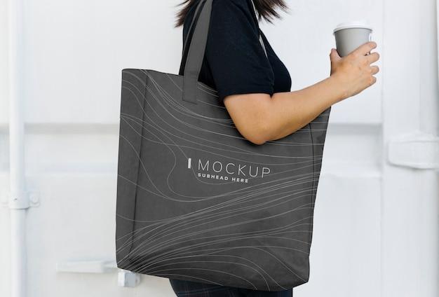 Frau, die ein schwarzes einkaufstaschemodell trägt Premium PSD