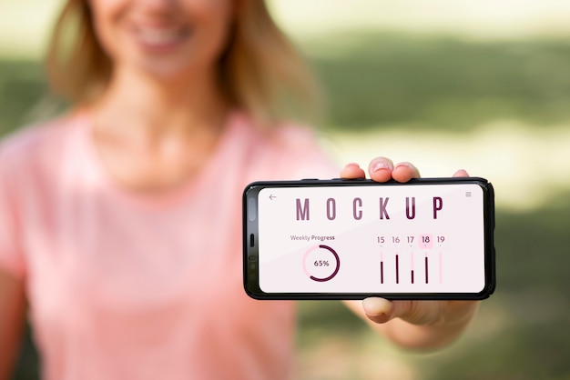 Frau, die ein telefon mit einem modellbildschirm im freien zeigt Kostenlosen PSD