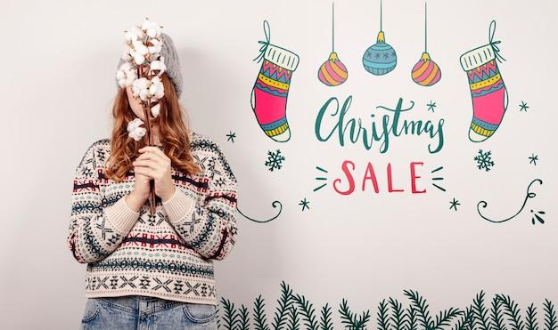 Frau, die eine weihnachtsstrickjacke und weihnachtsverkaufsangebote trägt Kostenlosen PSD