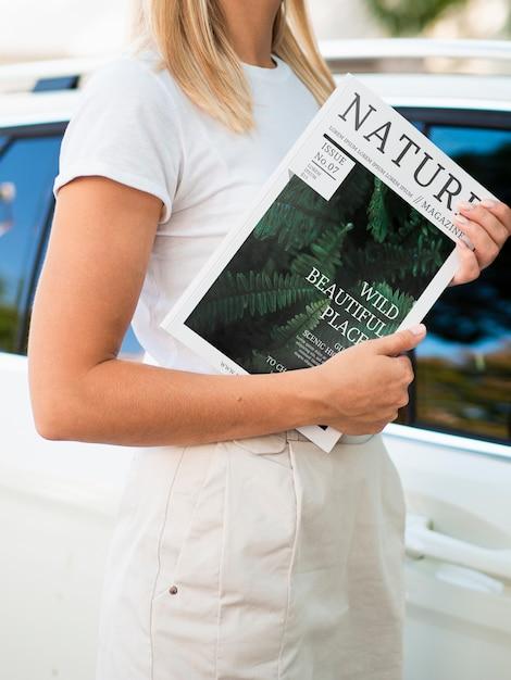 Frau, die eine zeitschrift nahe bei einem autospott hochhält Kostenlosen PSD