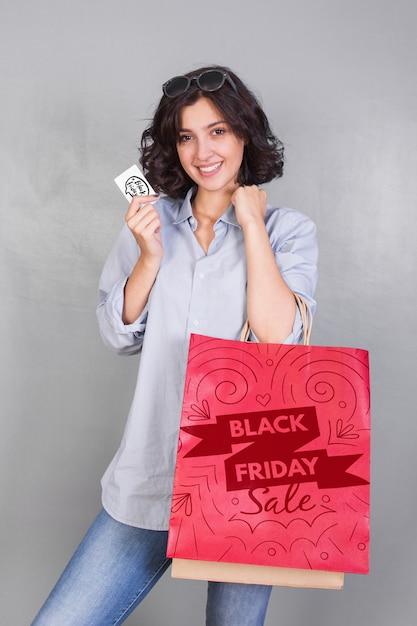 Frau, die einkaufstaschemodell mit schwarzem freitag-konzept hält Kostenlosen PSD