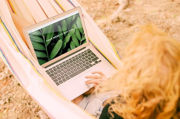 Frau, die laptopmodell in der natur verwendet Kostenlosen PSD