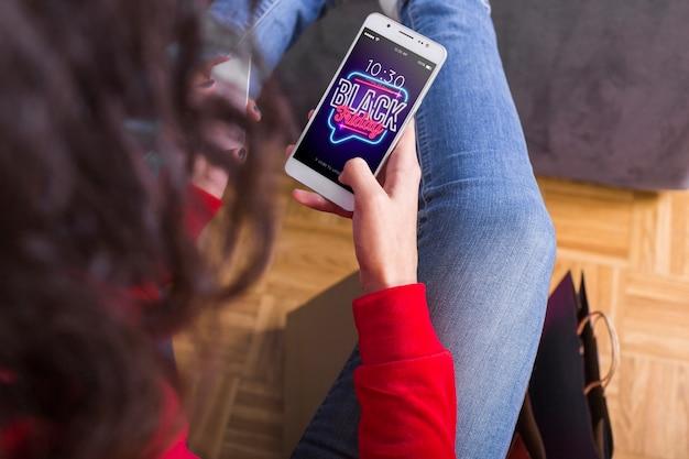 Frau, die nach schwarzem freitag auf smartphone sucht Kostenlosen PSD