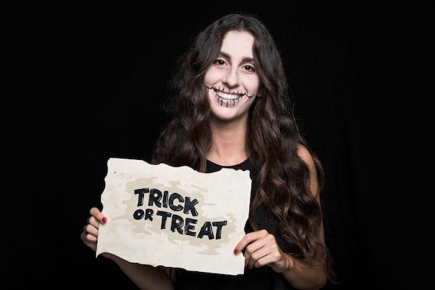 Frau, die papier mit halloween-beschriftung hält Kostenlosen PSD