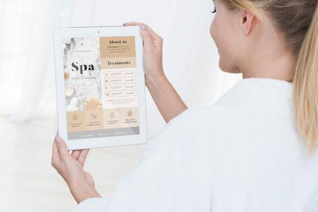 Frau, die tablettenmodell mit badekurortangeboten hält Kostenlosen PSD
