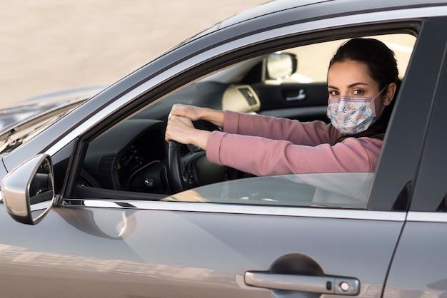 Frau im auto, die medizinische maske trägt Kostenlosen PSD