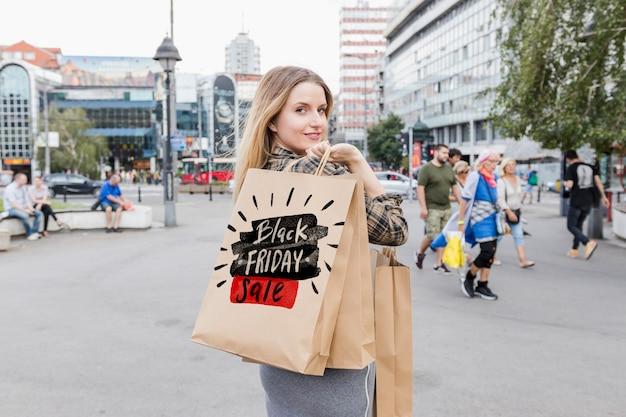 Frau in der stadt mit schwarzen freitag-taschen Kostenlosen PSD