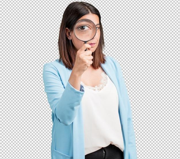 Frau mittleren alters überrascht und mit großen augen durch eine lupe suchen, etwas zu studieren, beweise zu finden, Premium PSD