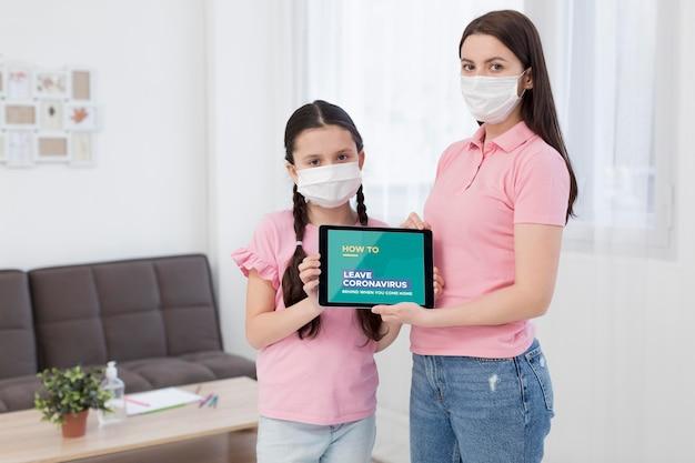 Frau und tochter halten ein tablettenmodell mit covid-19-präsentation Kostenlosen PSD