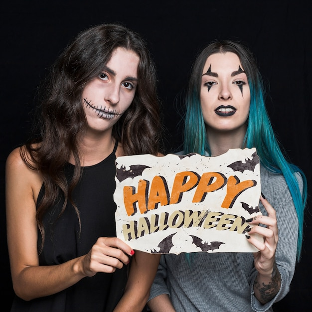 Frauen, die papier mit halloween-beschriftung halten Kostenlosen PSD