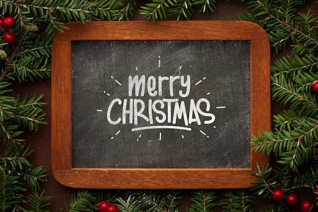 Frohe weihnachten auf tafel- und weihnachtskiefernblättern Kostenlosen PSD