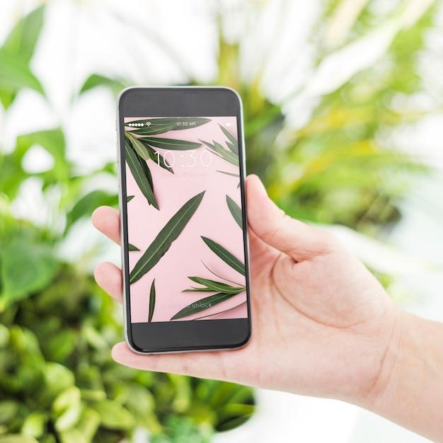 Gartenarbeitkonzept mit der hand, die smartphone hält Kostenlosen PSD