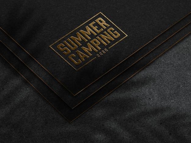 Geprägtes goldenes logo-modell auf dunklem papier Kostenlosen PSD