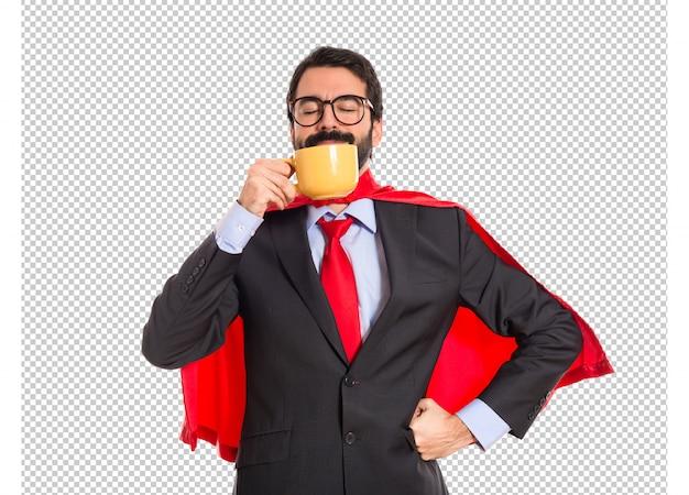 Geschäftsmann gekleidet wie trinkender kaffee des superhelden Premium PSD