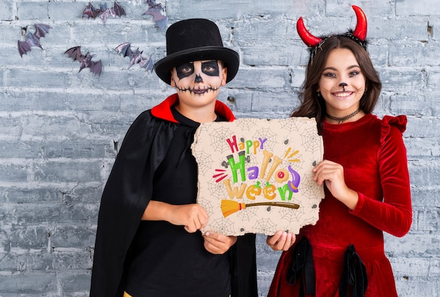 Geschwister, die einen mittleren schuss der glücklichen halloween-karte zeigen Kostenlosen PSD