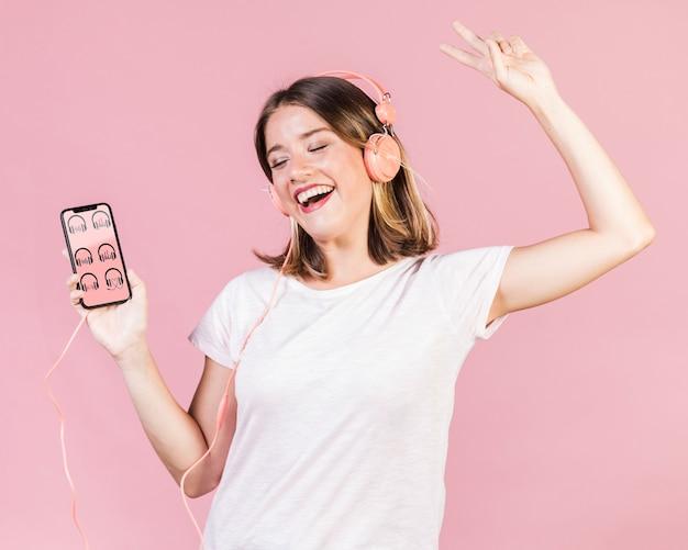 Glückliche junge frau mit den kopfhörern, die ein mobiltelefonmodell halten Kostenlosen PSD