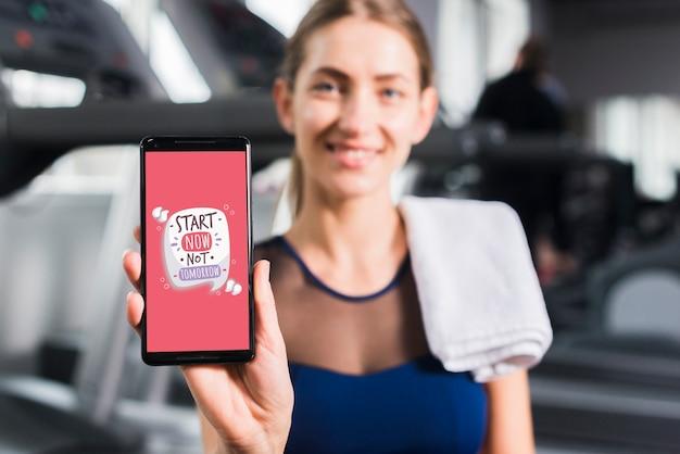 Glückliche sportliche frau, die smartphonemodell darstellt Kostenlosen PSD