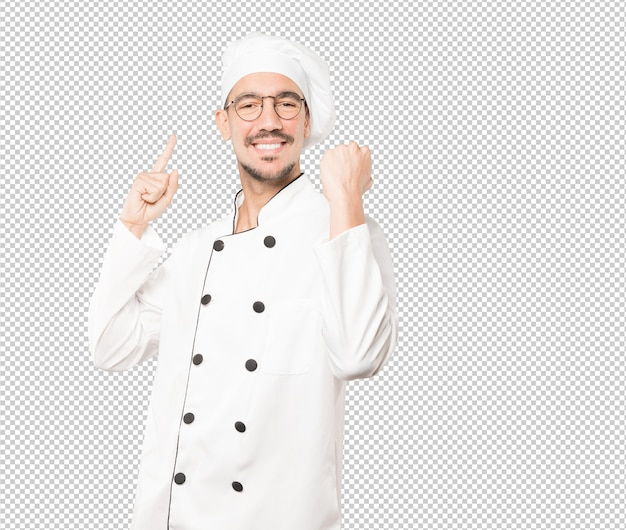 Glücklicher junger koch, der eine wettbewerbsfähige geste tut Premium PSD