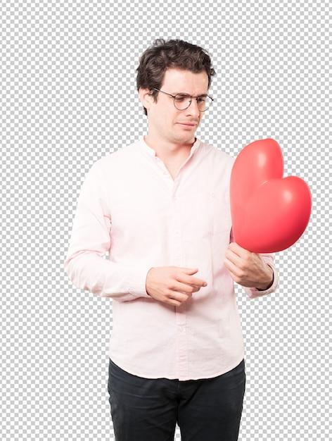 Glücklicher junger mann, der ein großes spielzeugherz hält und gesten über valentinstag tut Premium PSD