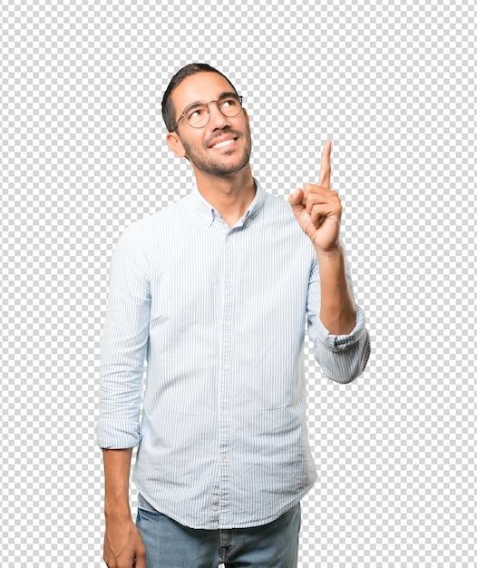 Glücklicher junger mann, der oben mit seinem finger zeigt Premium PSD